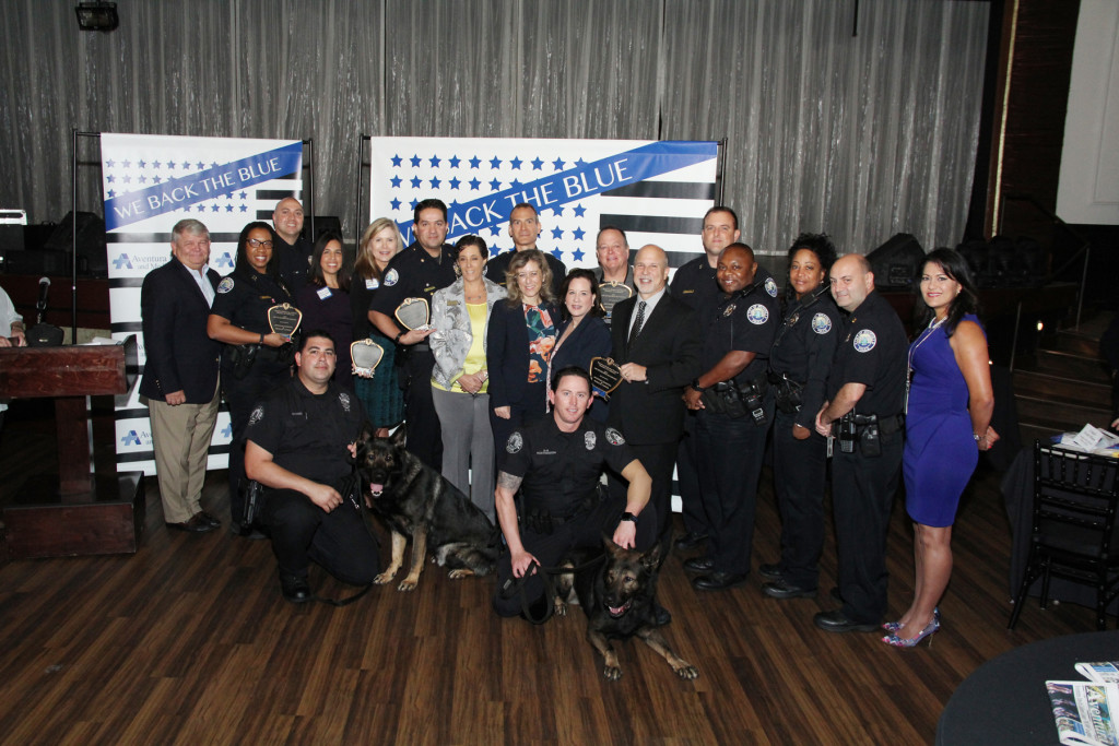 "(L to R) AMC Chairman Gary Pyott, Association 1st; Capt. Karyn Brinson and Ofc. Michael Mellides, Aventura Police Dept.; Vianca Larice and Luanne Ansaldo, Aventura Hospital and Medical Center; Maj. Mike Bentolila, Aventura Police Dept.; Aventura Comm. Gladys Mezrahi and Police Chief Bryan Pegues; Alisa Bert, Aventura Hospital and Medical Center; Aventura Mayor Enid Weisman, Maj. William ""Skip"" Washa, City Manager Eric Soroka; Capt. Madison Freeman, Ofc. Elricco Barnes, Ofc. Carolyn Gray, Capt. Thomas Labombarda and Exec. Asst. Rita Noa, Aventura Police Dept.  (Front Center) Ofc. Luis Chaidez with K9 Franklin and Ofc. Brandon Worthington with K9 Chulligan, Aventura Police Dept."